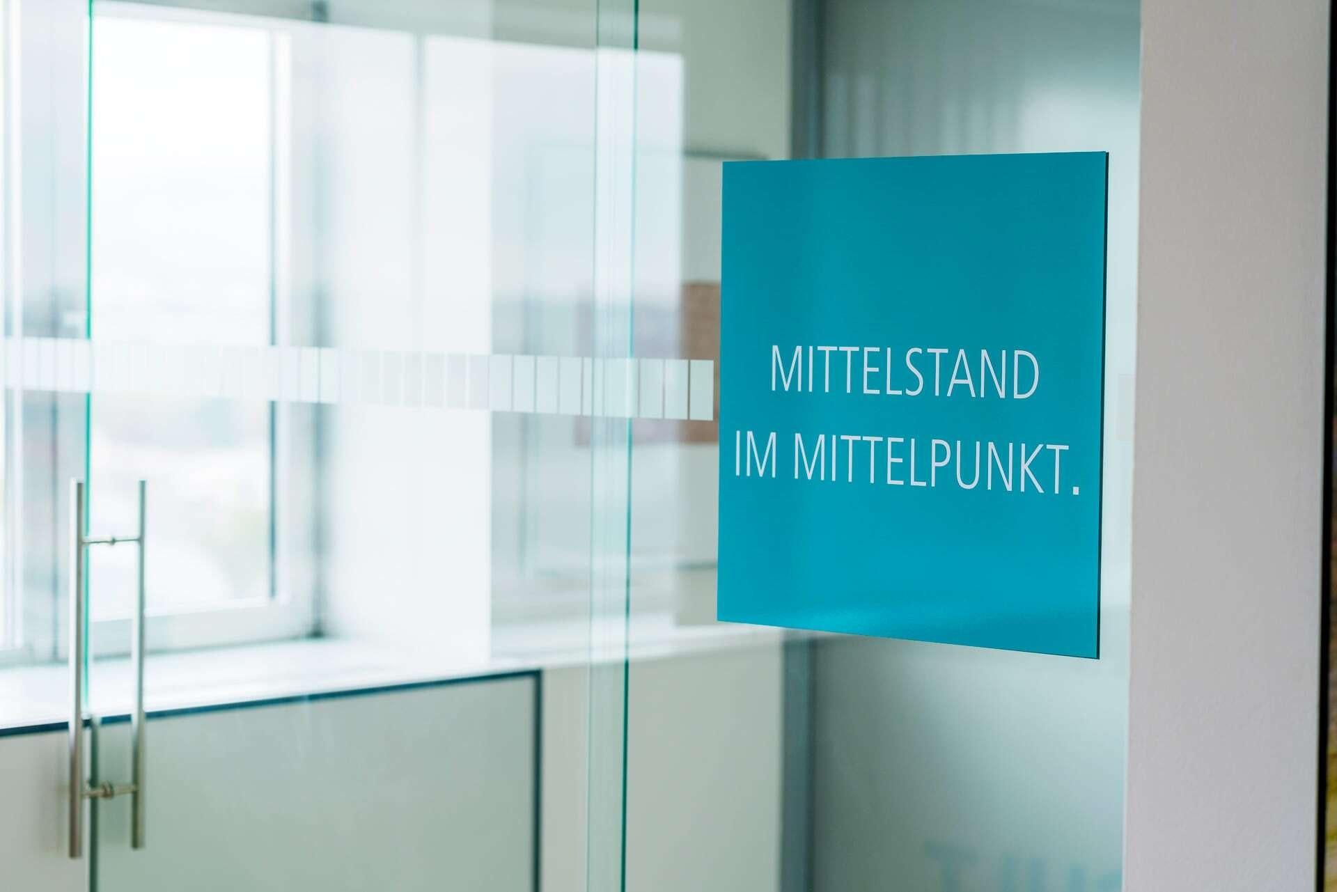 Nahaufnahme einer Glastüre mit dem Uniconsult Slogan Mittelstand im Mittelpunkt